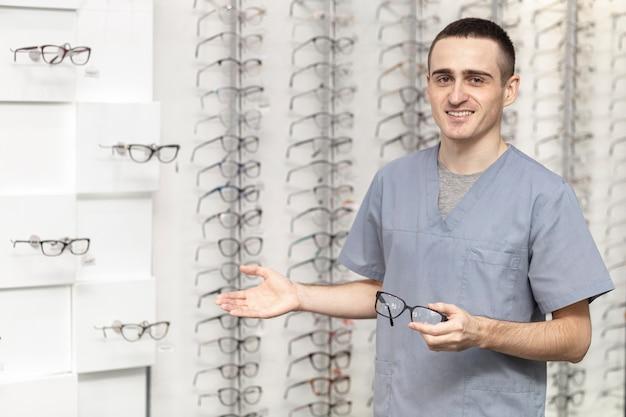 Vista frontal del hombre sonriente con par de anteojos en la mano Foto gratis