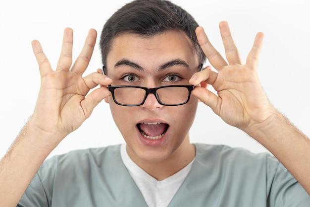 Vista frontal del hombre sonriente sosteniendo sus gafas en la cara Foto gratis