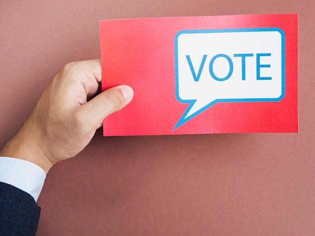 Vista frontal hombre sosteniendo una tarjeta roja con bocadillo de votación Foto gratis