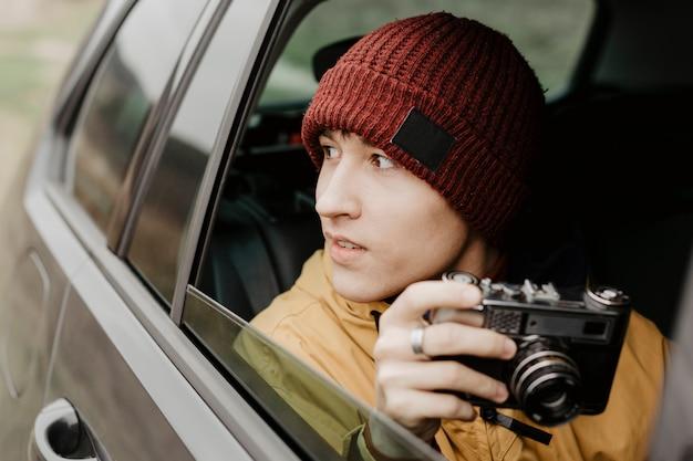 Vista frontal hombre sujetando la cámara Foto gratis