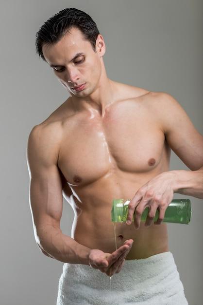 Vista frontal hombre vertiendo champú en mano Foto gratis