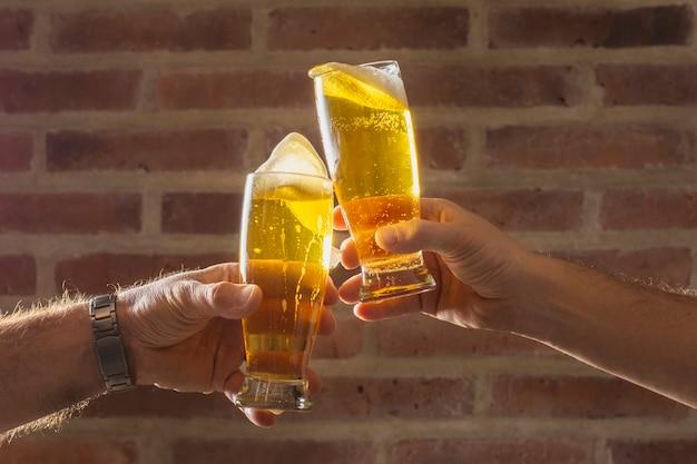 Vista frontal hombres animan con vaso de cerveza Foto gratis
