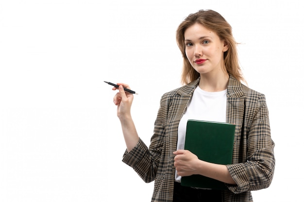 Una vista frontal joven bella dama en camiseta blanca jeans negros y abrigo con libro verde y bolígrafo sonriendo en el blanco Foto gratis
