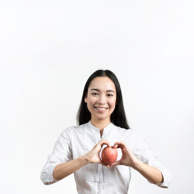 Vista frontal de la joven y bella mujer haciendo forma de corazón con manzana roja de pie sobre fondo blanco Foto gratis