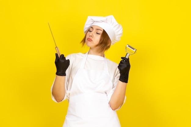 Una vista frontal joven cocinera en traje de cocinero blanco y gorra blanca en guantes negros con cuchillo y limpiador de verduras en el amarillo Foto gratis