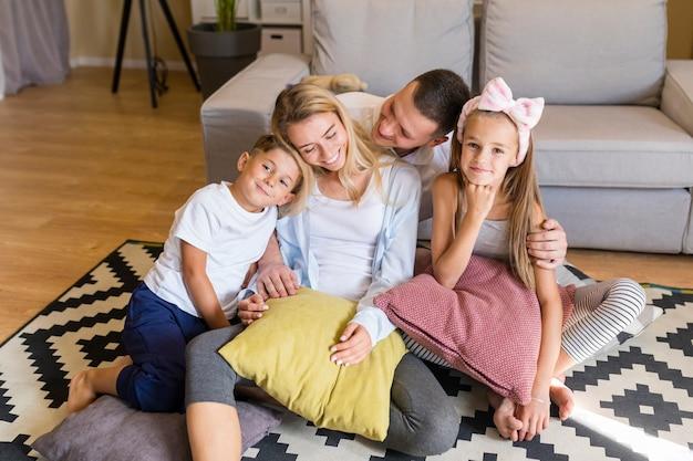 Vista frontal joven familia pasar tiempo en la sala de estar Foto gratis
