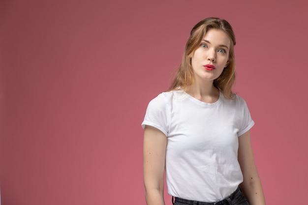 Vista frontal joven mujer atractiva en camiseta blanca posando con expresión de sorpresa en la pared rosa modelo pose femenina color hembra joven Foto gratis