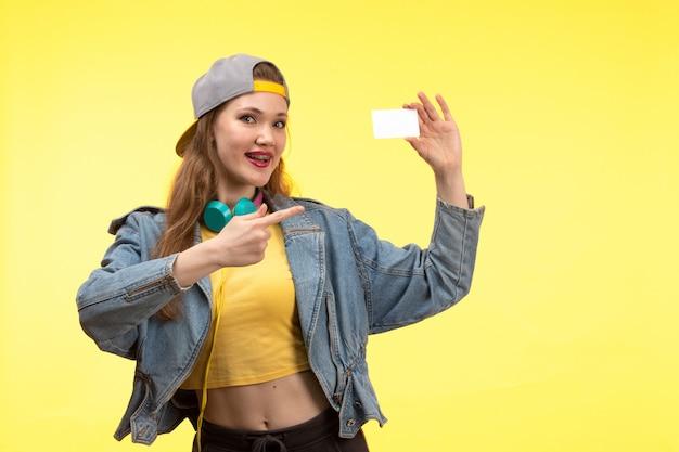 Una vista frontal joven mujer moderna en camisa amarilla pantalón negro y abrigo de jean con auriculares de colores sonriendo Foto gratis