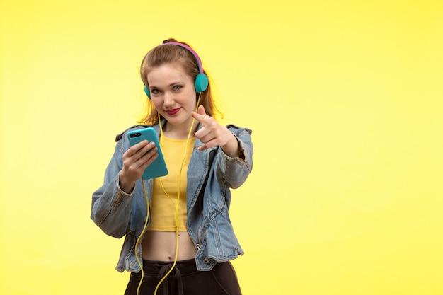 Una vista frontal joven mujer moderna en camisa amarilla pantalón negro y abrigo de jean con auriculares de colores con teléfono posando Foto gratis
