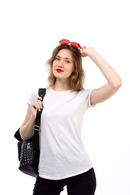 Una vista frontal jovencita en camiseta blanca gafas de sol rojas bolso negro sonriendo en el blanco Foto gratis