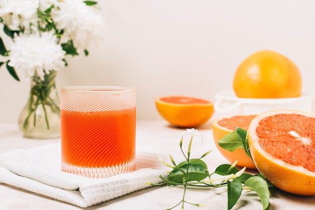 Vista frontal de jugo de pomelo en un vaso Foto gratis