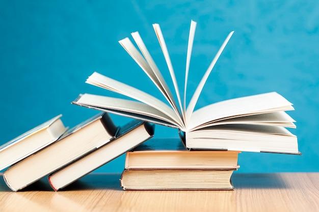 Vista frontal de libros sobre la mesa con fondo azul. Foto gratis