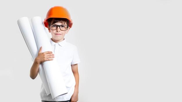 Vista frontal lindo niño con casco de seguridad Foto gratis