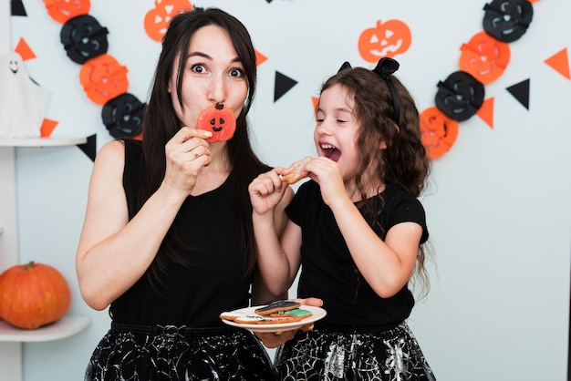 Vista frontal de la madre y la hija comiendo galletas Foto gratis