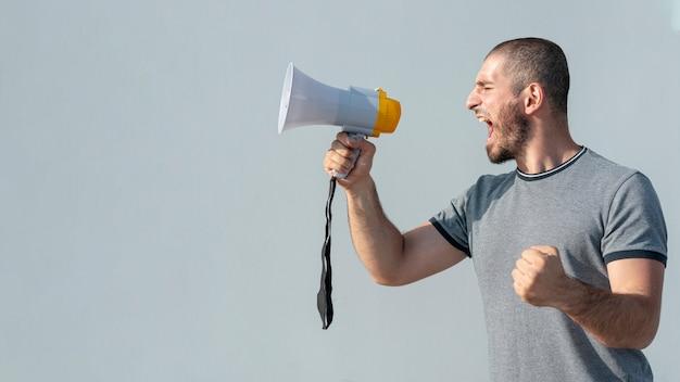 Vista frontal manifestante con megáfono gritando Foto gratis