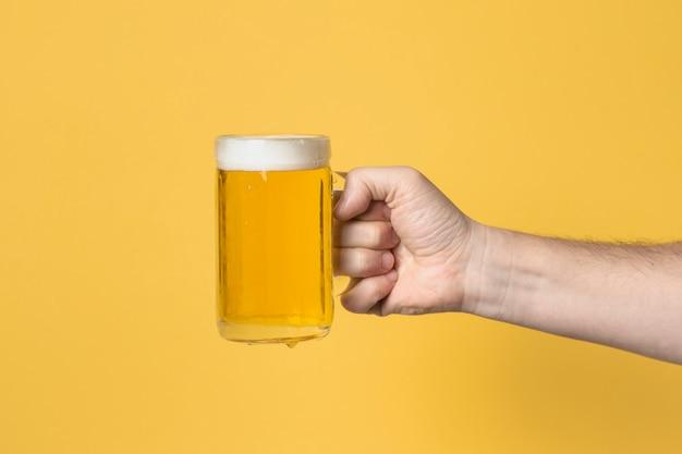 Vista frontal de la mano con jarra de cerveza Foto Premium