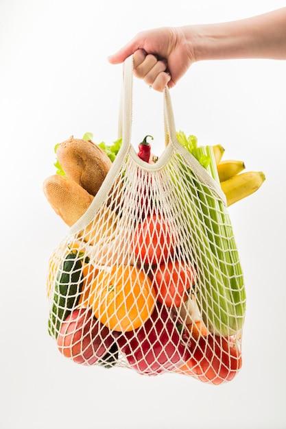 Vista frontal de la mano que sostiene la bolsa reutilizable con frutas y verduras Foto Premium