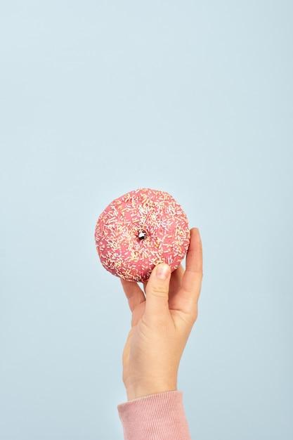 Vista frontal de la mano que sostiene donut glaseado con chispas Foto gratis