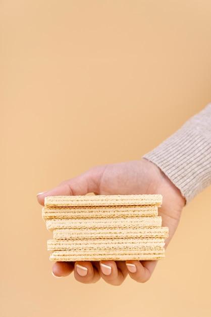 Vista frontal de la mano sujetando obleas con espacio de copia Foto gratis
