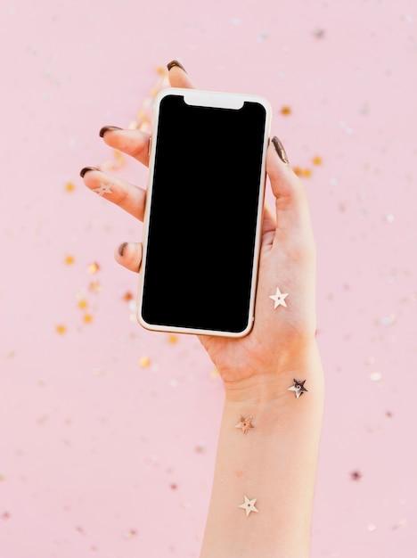 Vista frontal mano sujetando un teléfono móvil Foto gratis