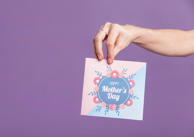 Vista frontal mano con tarjeta de felicitación Foto gratis