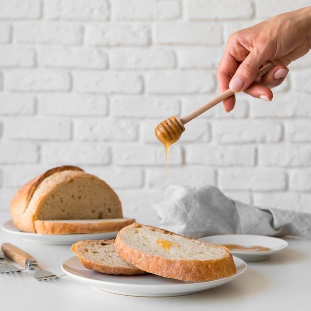 Vista frontal mano vertiendo miel sobre rebanada de pan Foto gratis