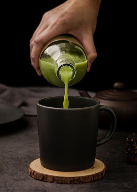 Vista frontal de la mano vertiendo té matcha en taza Foto gratis