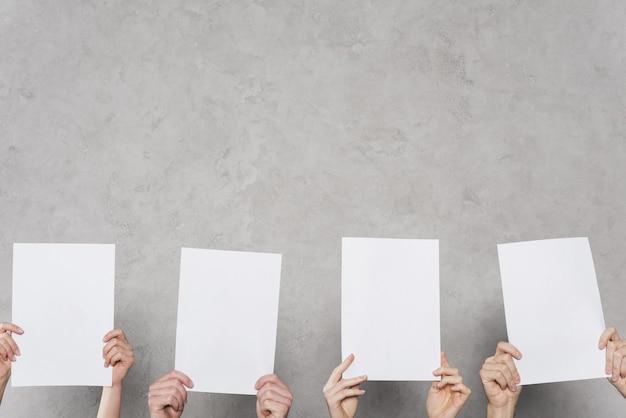 Vista frontal de manos sosteniendo papeles en blanco con espacio de copia Foto Premium