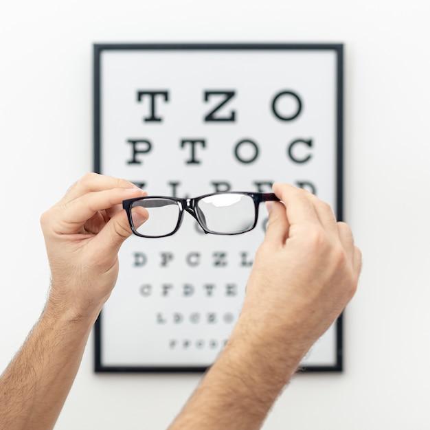 Vista frontal de manos sosteniendo un par de anteojos con prueba ocular desenfocada en el fondo Foto Premium