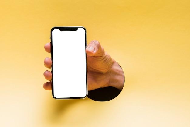 Vista frontal maqueta smartphone sostenido por persona Foto gratis