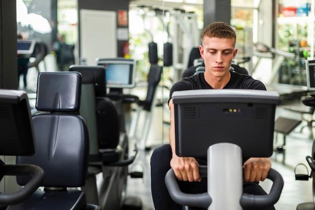 Vista frontal masculino en el gimnasio en bicicleta Foto gratis