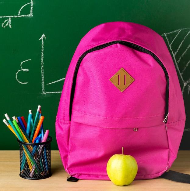 Vista frontal de la mochila para el regreso a la escuela con manzana y lápices. Foto gratis