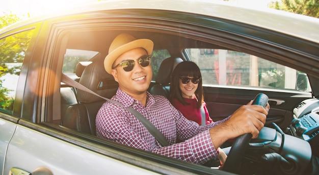 Vista frontal del momento divertido par asiático hombre y mujer sentada en el coche. disfrutando el concepto de viaje. Foto Premium