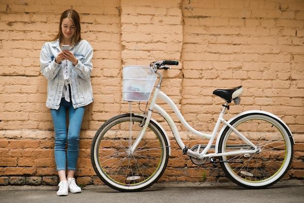 Vista frontal mujer apoyada contra una pared Foto gratis