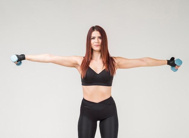 Vista frontal de la mujer atlética en atuendo de gimnasio haciendo ejercicios con pesas Foto gratis