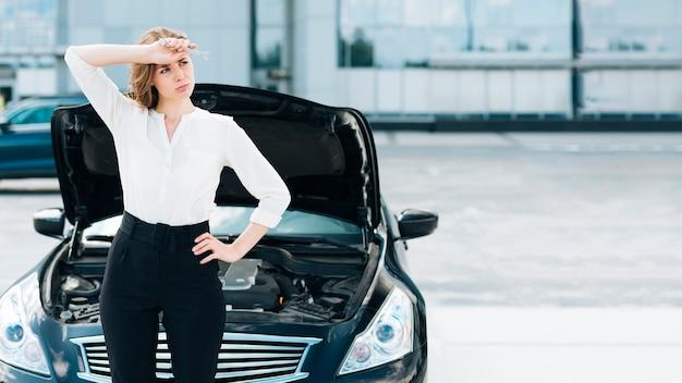 Vista frontal, de, mujer y coche Foto gratis