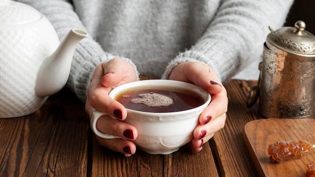 Vista frontal de la mujer con el concepto de té Foto gratis