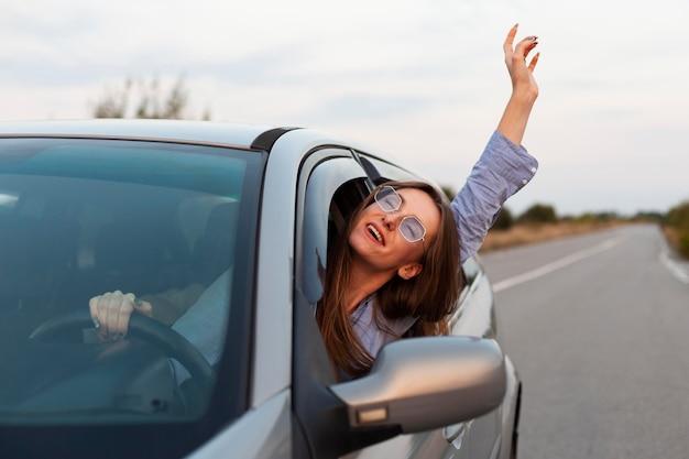 Vista frontal de la mujer conduciendo y divirtiéndose Foto gratis
