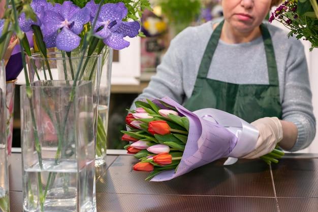 Vista frontal mujer envolviendo tulipanes Foto gratis