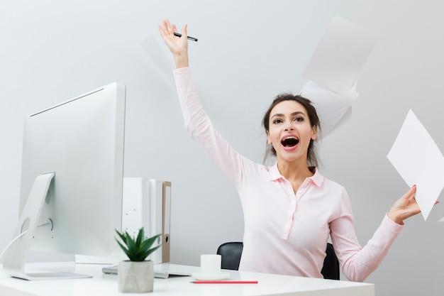 Vista frontal de la mujer extática en el trabajo tirando papeles Foto gratis