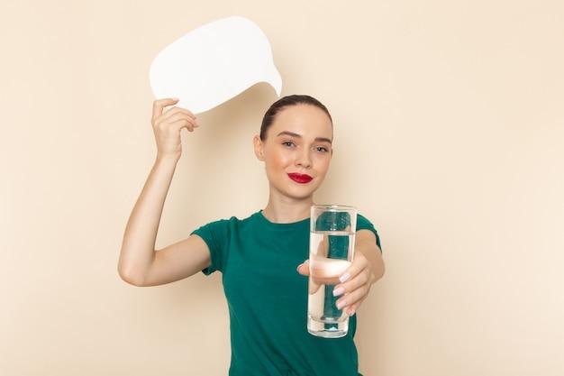 Vista frontal mujer joven en camisa verde oscuro y jeans con vaso de agua y cartel blanco en beige Foto gratis
