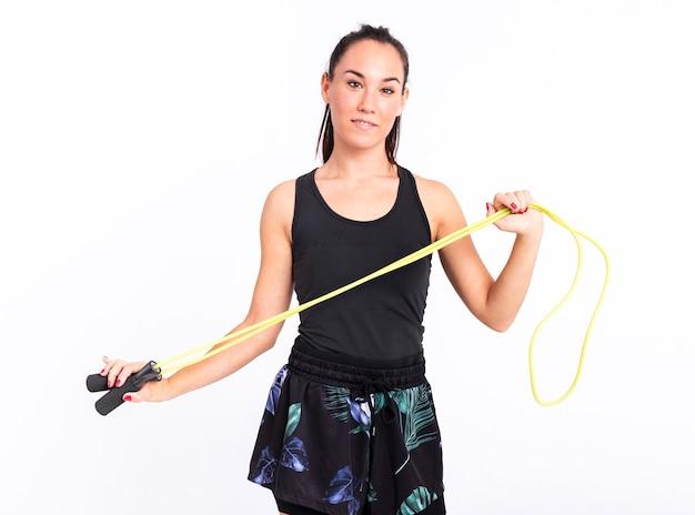 Vista frontal mujer joven con saltar la cuerda Foto gratis