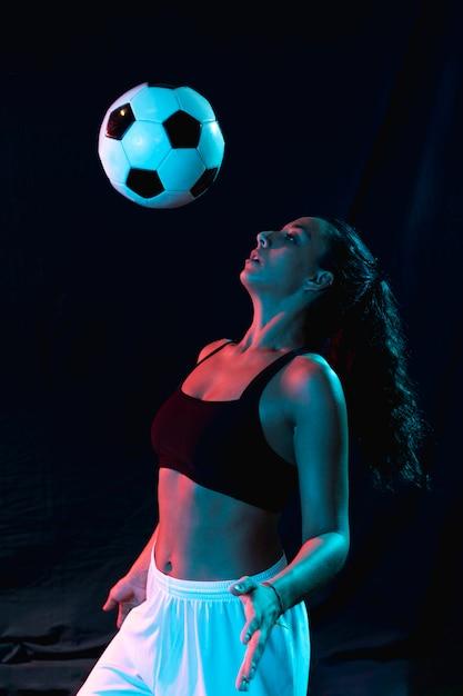 Vista frontal mujer jugando con balón de fútbol Foto gratis