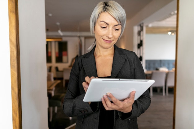 Vista frontal mujer de negocios con tableta Foto gratis