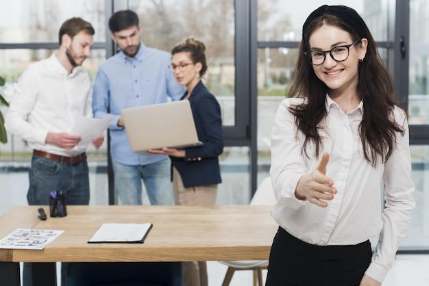 Vista frontal de la mujer en la oficina ofreciendo apretón de manos Foto Premium