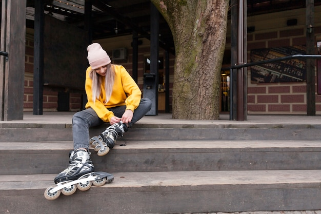 Vista frontal de la mujer en patines sentado en las escaleras Foto gratis