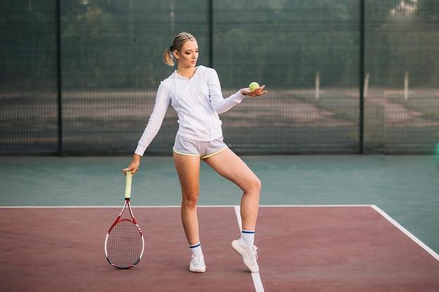 Vista frontal mujer posando en el campo de tenis Foto gratis