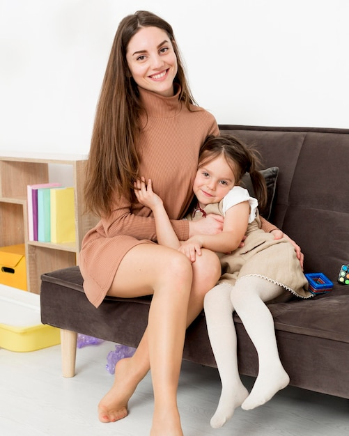 Vista frontal de la mujer posando con niña Foto gratis