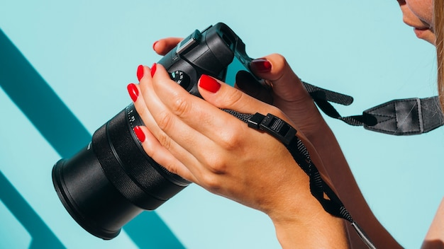 Vista frontal mujer revisando fotos en la cámara Foto gratis