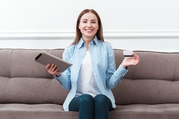 Vista frontal mujer sentada en el sofá con tableta digital y tarjeta de crédito Foto gratis